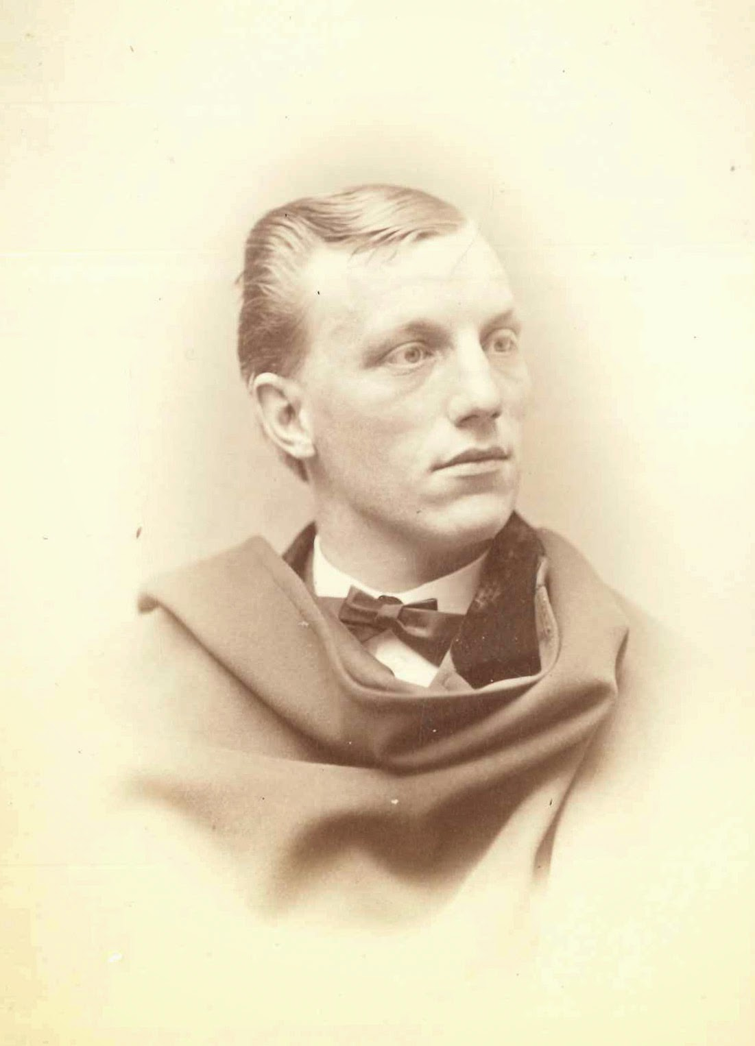A photograph of a man with cloth draped around his shoulders.