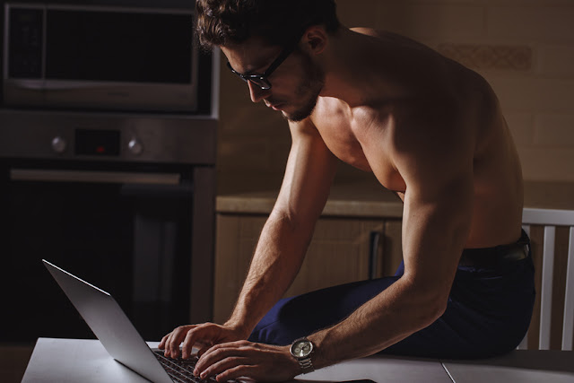 Physically Fit Man Using Laptop at home