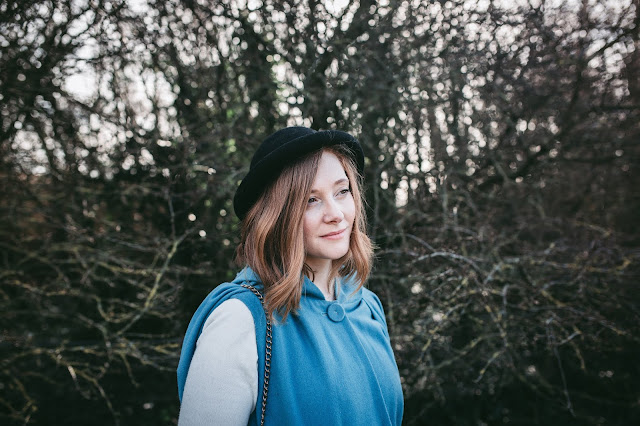 image shows a young woman standing in front of some trees and looking off camera. She is wearing a blue coat and bowler hat.