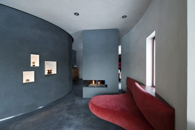 Photo of red sofa by the fireplace on the dark grey wall in the living room