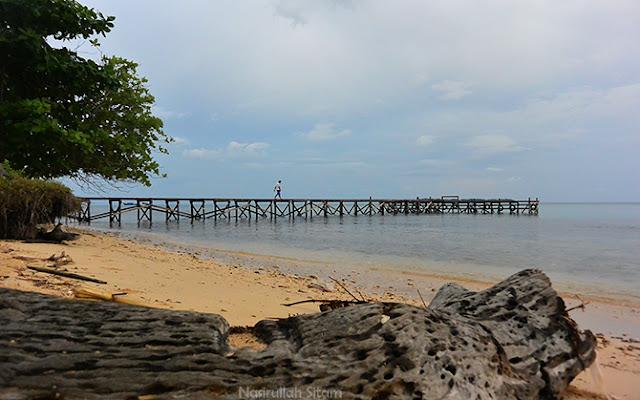 Pemandangan pantai yang ada dermaga kayunya