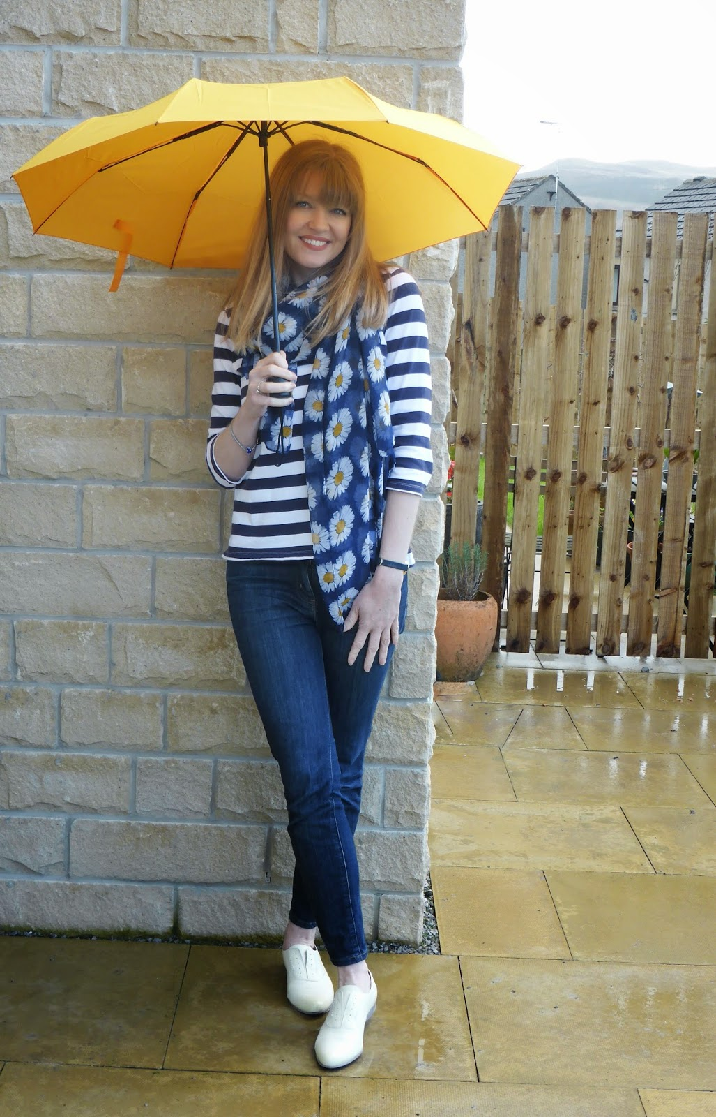 Over 40 blogger What Lizzy Loves wearing Jack Wills breton, Clarks yellow brogues, a floral scarf and Boden jeans with a yellow umbrella