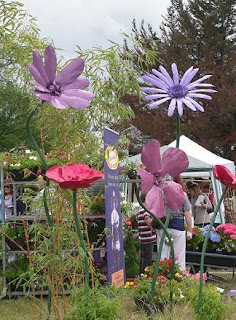Giant purple and red model flowers with a gazebo and trees in the background