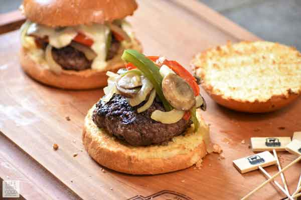 Assembling Philly Cheese Steak Burgers with vegetables on top