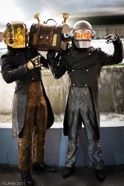 Steampunk Daft Punk Costumes in gold and silver with steampunk musical wooden chest with boombox. LED light up metal helmets, brocade pants and coats. Steampunk Fashion