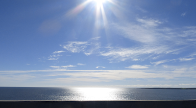 The starry rays of the sun against a blue, lightly clouded sky are reflected on a darker blue ocean