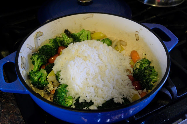 The prepared rice being added to the dutch oven with the vegetables.