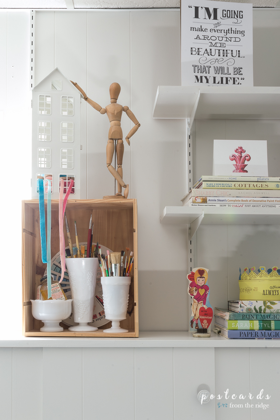 Wooden art mannequin and art brushes in milk glass vases