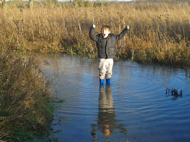 A boy in a huge puddle.
