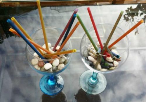 un vaso adornado con piedras y pajitas que dentro tienen gelatina de mojito