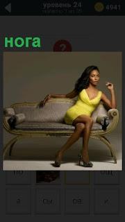 В помещении сидит девушка в желтом платье, положив ногу на ногу в красивой позе