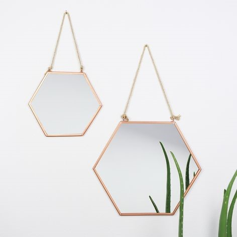 Two geometric shaped mirrors hanging on a wall