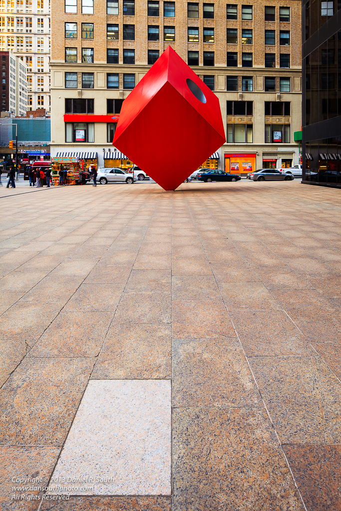 a photo of the red cube statue in new york with a white tile