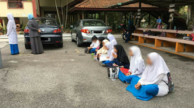 tindakan sekolah 'mendenda' pelajar yang datang lewat ke tapak perhimpunan dengan duduk di atas tar
