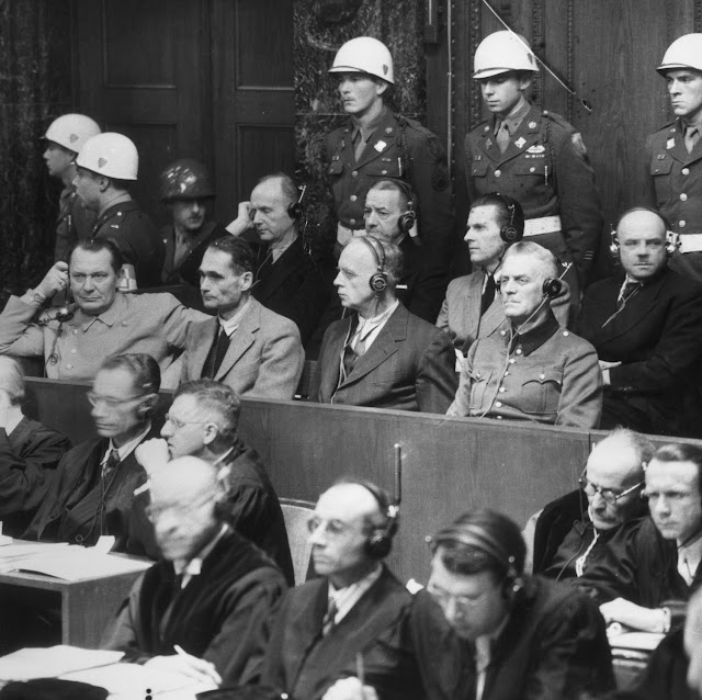 The Nuremberg trial of high profile Nazi war criminals (November 22, 1945) Front row, left to right: Hermann Göring, Rudolf Hess, Joachim von Ribbentrop, and Wilhelm Keitel; Back row, left to right: Karl Dönitz, Erich Raeder, Baldur von Schirach, and Fritz Sauckel