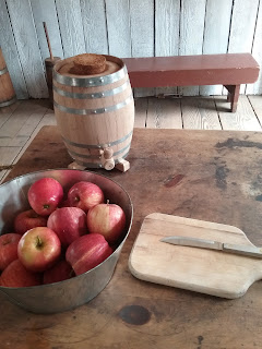 Oak barrel for cider-making, twelve apples, and cutting board.