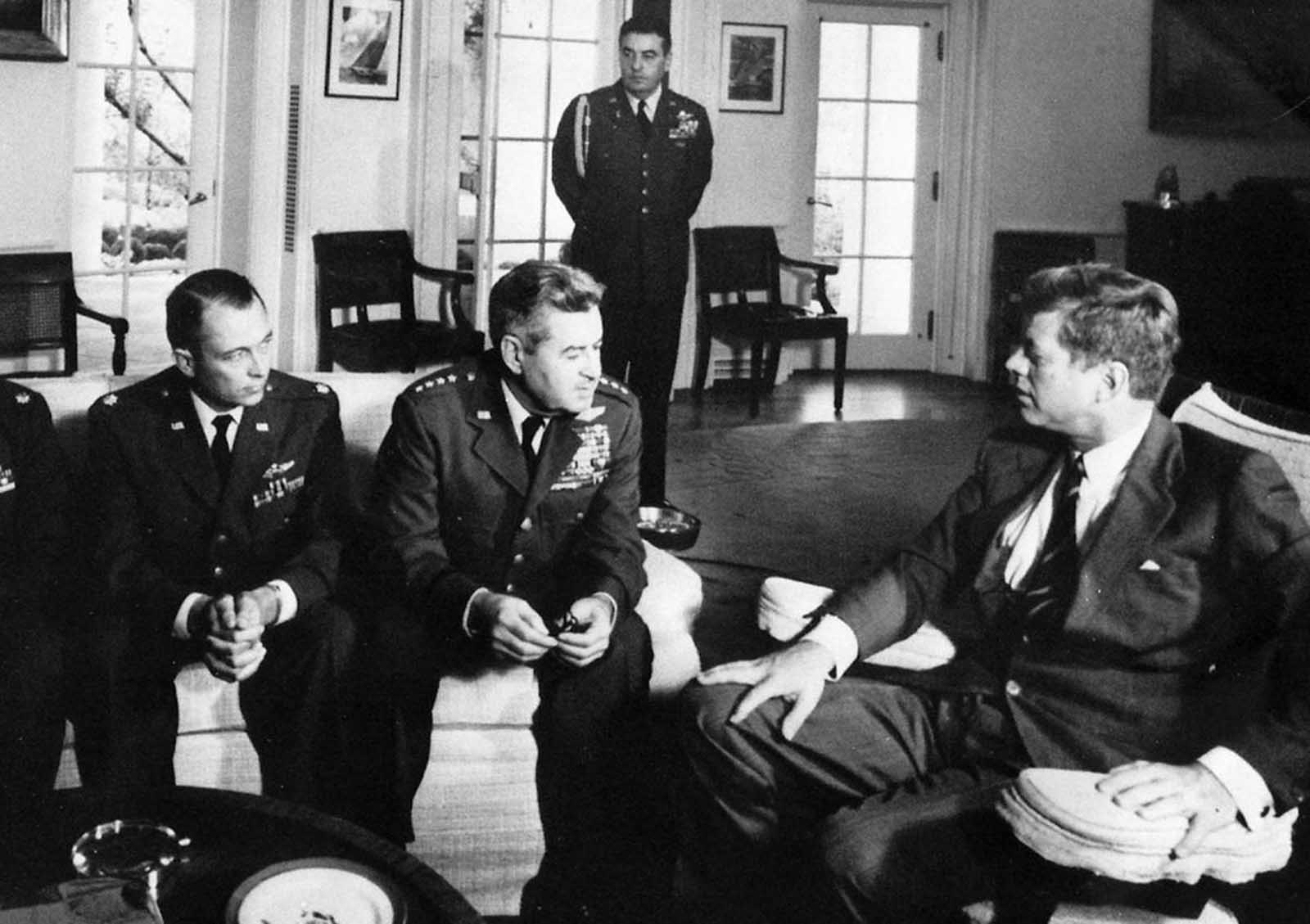 President John F. Kennedy meets with Air Force Maj. Richard Heyser, left, and Air Force Chief of Staff, Gen. Curtis LeMay, center, at the White House in Washington to discuss U-2 spy plane flights over Cuba.