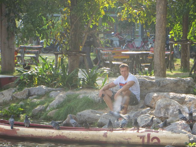 Парень сидит у озера с голубями