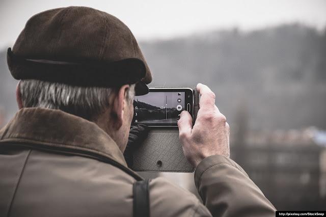 Varón tomando una fotografía con su teléfono