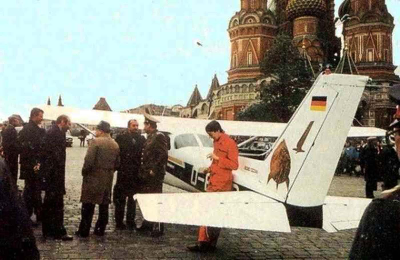 Rust's Cessna 172, resting near Red Square some time after his landing. Rust is standing on the right in the photo, wearing colored overalls.