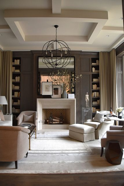 coffered ceiling, brown walls and bookcases and beige and light pink upholstered furniture