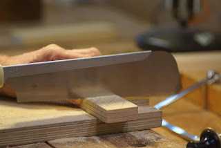 Image of a Japanese saw being used to cut the shoulders of a tenon joint.