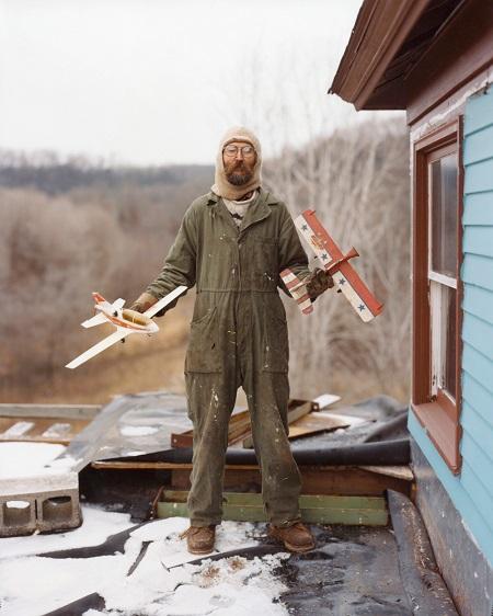 hombre sosteniendo dos aviones de juguete con gorro de piloto