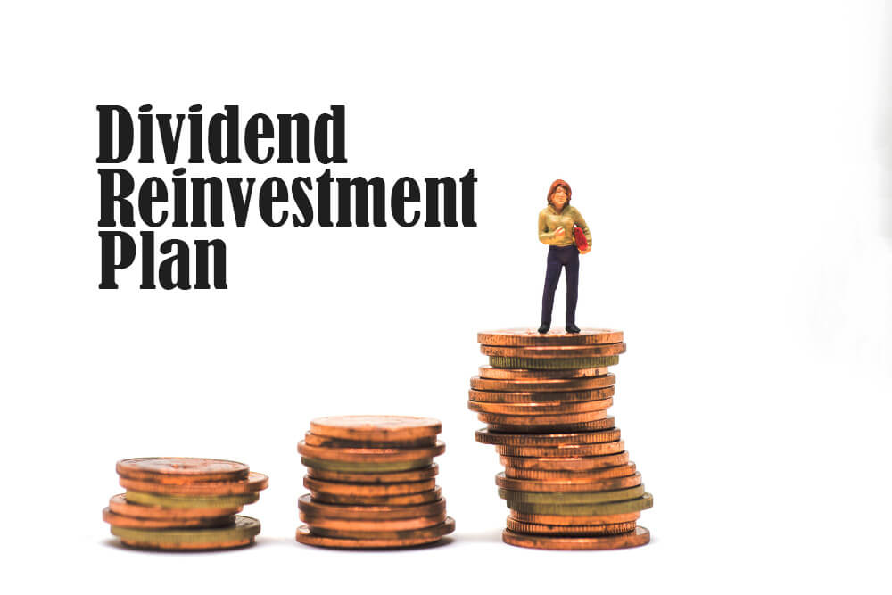 woman standing on top of stack of coins with words dividend reinvestment plan