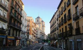 Primer tramo de la calle desde la plaza Mayor, al fondo la iglesia de San Isidro.A ambos lados edificos de vivienas de cuatro plantas con balcones.