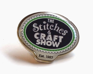 "Rounded enamelled badge with the rounded logo which says ""The Stitches & CRAFT SHOW Est. 1987"""