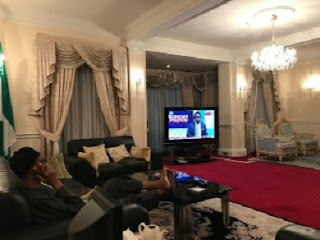 Photo Of 'Dead' Buhari Watching Aide On ChannelsTV Interview From UK Holiday