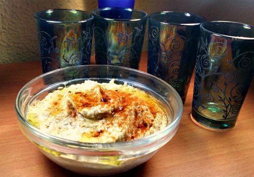 Un bol con hummus (garbanzos, comino y tahini) decorado con 4 vasos árabes