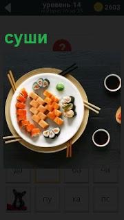 В тарелке лежит приготовленное блюдо суши с палочками для еды и вокруг чашки с напитком