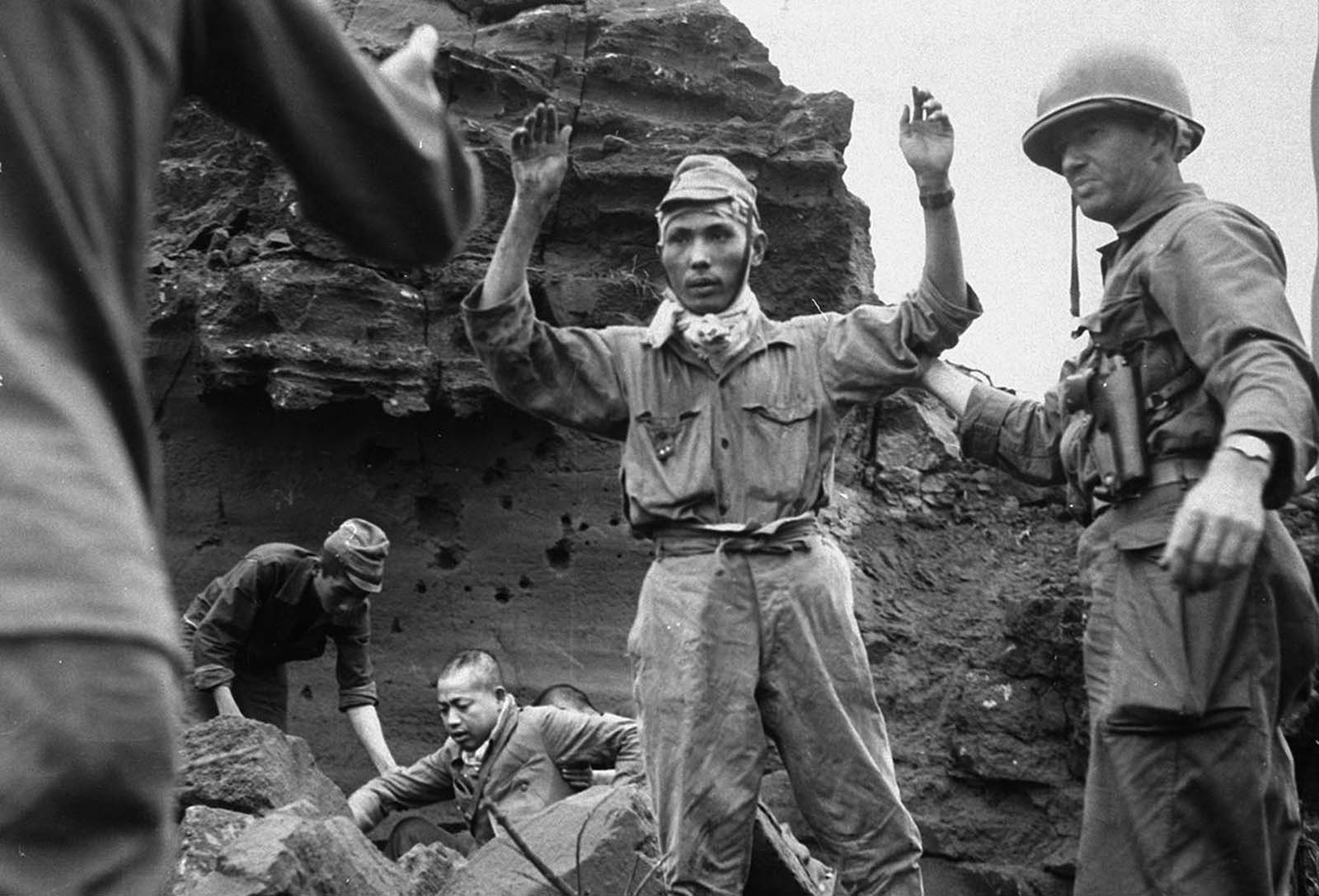 With his hands in the air, the first of 20 Japanese emerges from a cave on Iwo Jima, on April 5, 1945. The group had been hiding for several days.