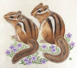 two embroidered chipmunks sitting on a bed of little purple flowers