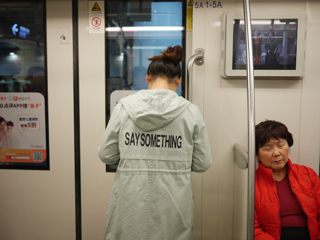 "young woman wearing a jacket with ""SAY SOMETHING"" on the back"