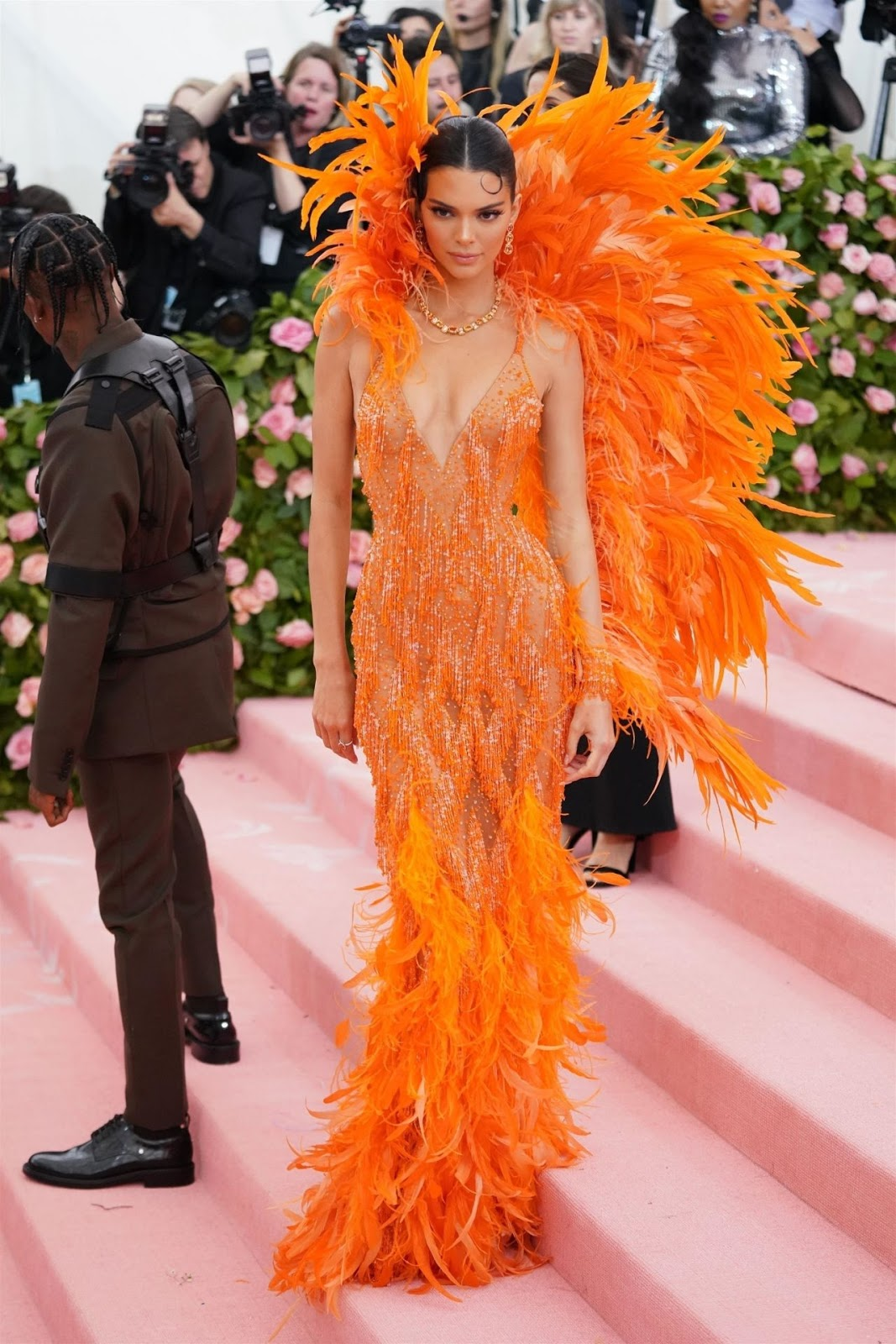 Kendall stunned in a Cher-inspired bright orange feathered naked dress