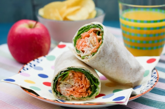A Carrot and Spinach Crunch Lunch Wrap on a spotty paper napkin, served beside a red apple and a glass of orange juice