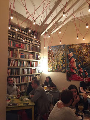 Bar Tongs interior design with books and wall paintings for aperitivo in Navigli Milan