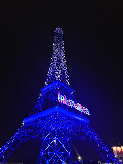 Eiffel Tower with Lollapalooza sign lit up at night