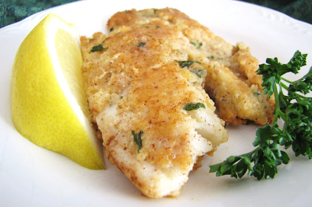almond-crusted tilapia with lemon wedge and parsley