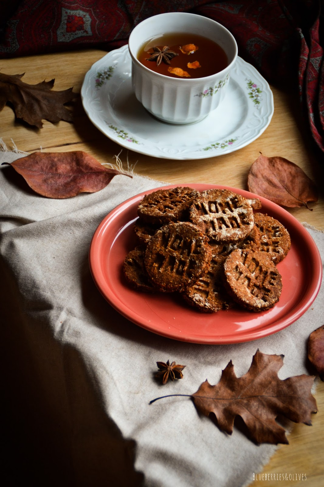 homemade cookies on red ceramic dish, dark background, old wood, piles books with red apple on top, porcelain mug with tea, star anise and orange peels