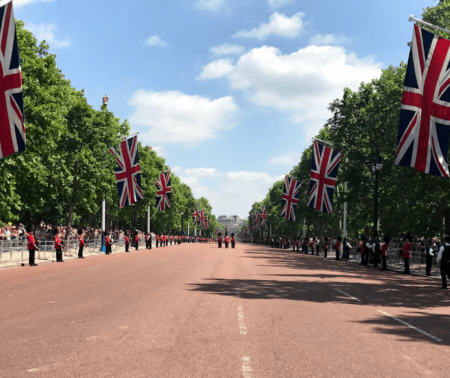 Queen's Guards parade, the road is lined with Union Jacks and the soldiers are walking towards the camera