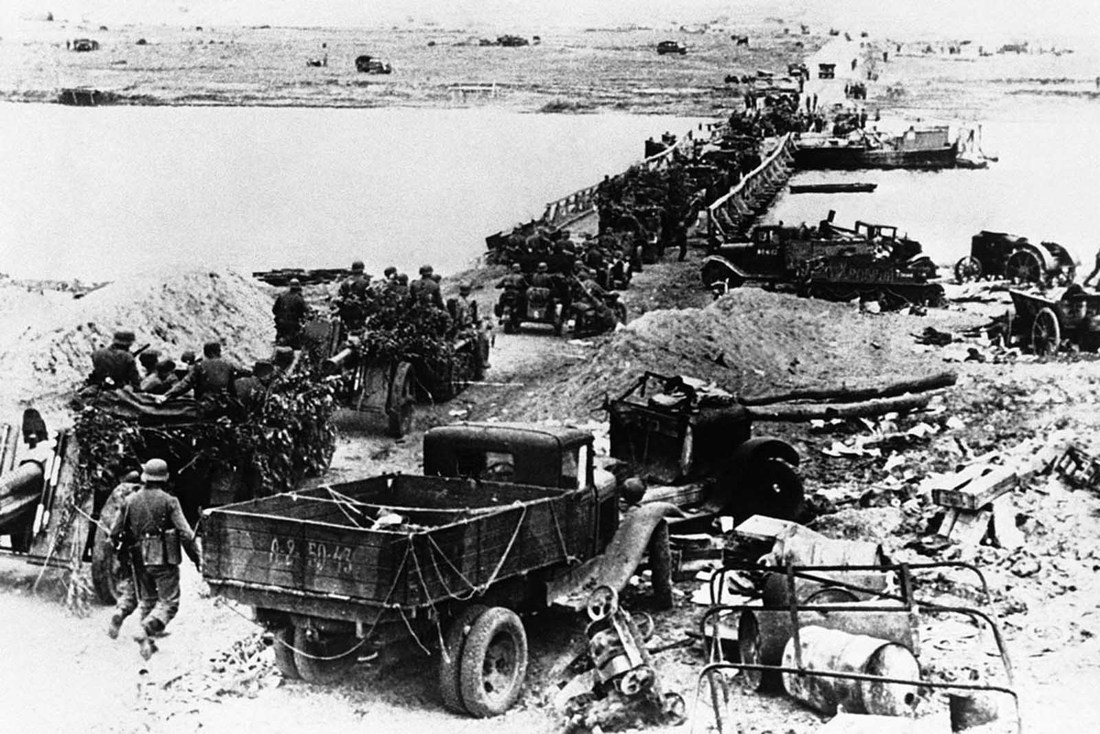 A German motorized artillery column crossing the Don river by means of a pontoon bridge on July 31, 1942. Wrecked equipment and materiel of all kinds lies strewn around as the crossing is made.