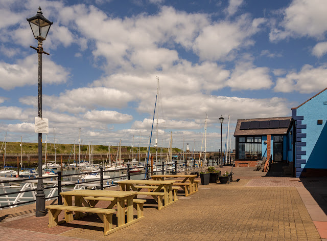Photo of new picnic benches on the paving overlooking the pontoons