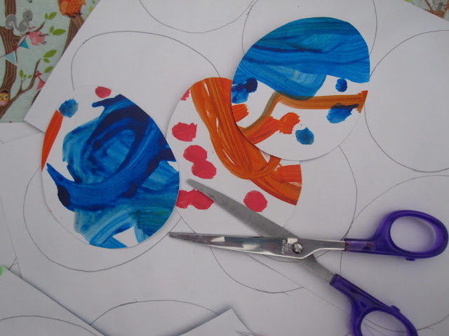 Multi-coloured egg shaped pieces of card next to a pair of scissors