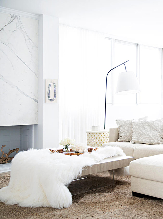 Chic living room in pure whites and a gorgeous marble fireplace. Image by Brittany Ambridge via Domino