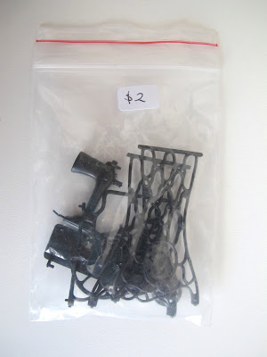 Plastic bag containing parts of a dolls' house miniature vintage sewing machine kit.