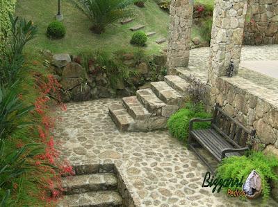 Construção do muro de pedra bruta com dois tipos de muro de pedra, o tipo de muro faceado e o tipo de muro de pedra sem cimento com nichos na pedra para execução do paisagismo com o piso de pedra rústico, a escada de pedra e os pilares de pedra.