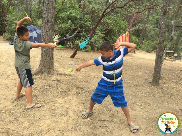 Two boys dueling with play swords while camping